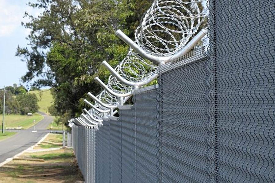 Колючая проволока на металлическом заборе