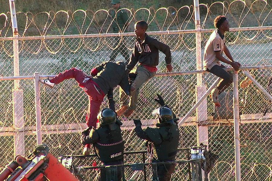 Мигранты, перелезающие через колючую проволоку в Испании