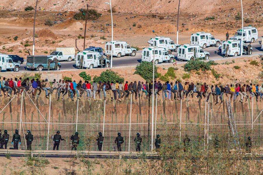 Мигранты на заборе с колючей проволокой в Сеуто