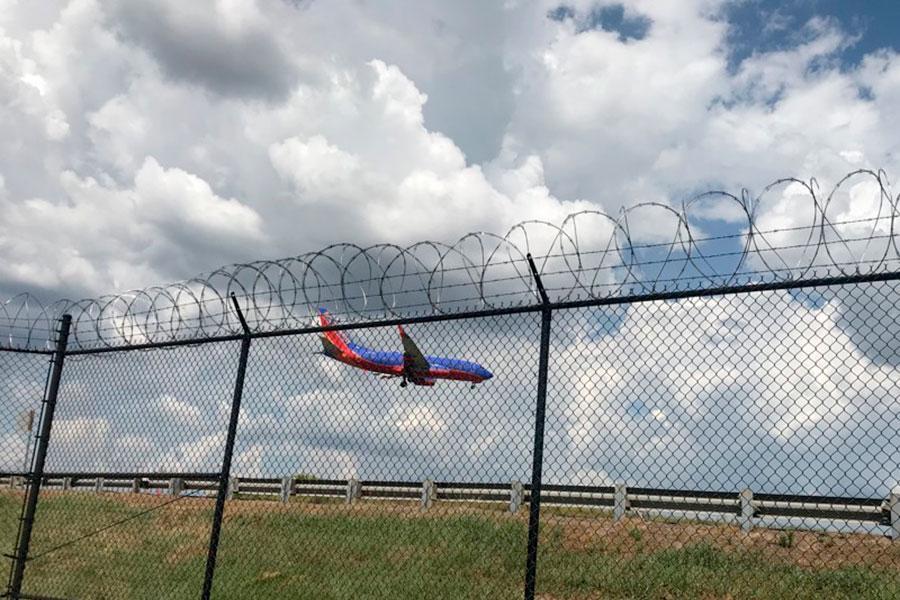 Забор со спиральным заграждением из колючей проволоки в аэропорту