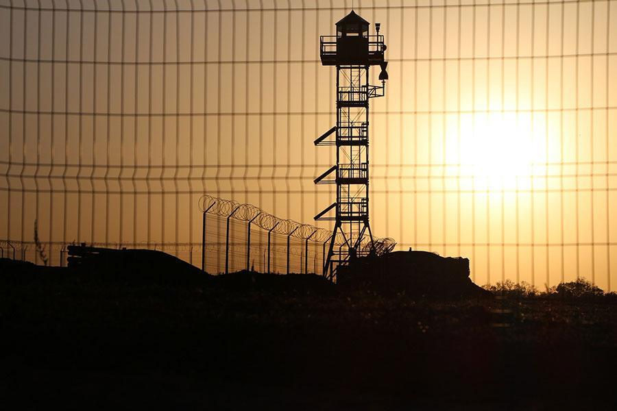 Колючая проволока и забор на границе с Россией