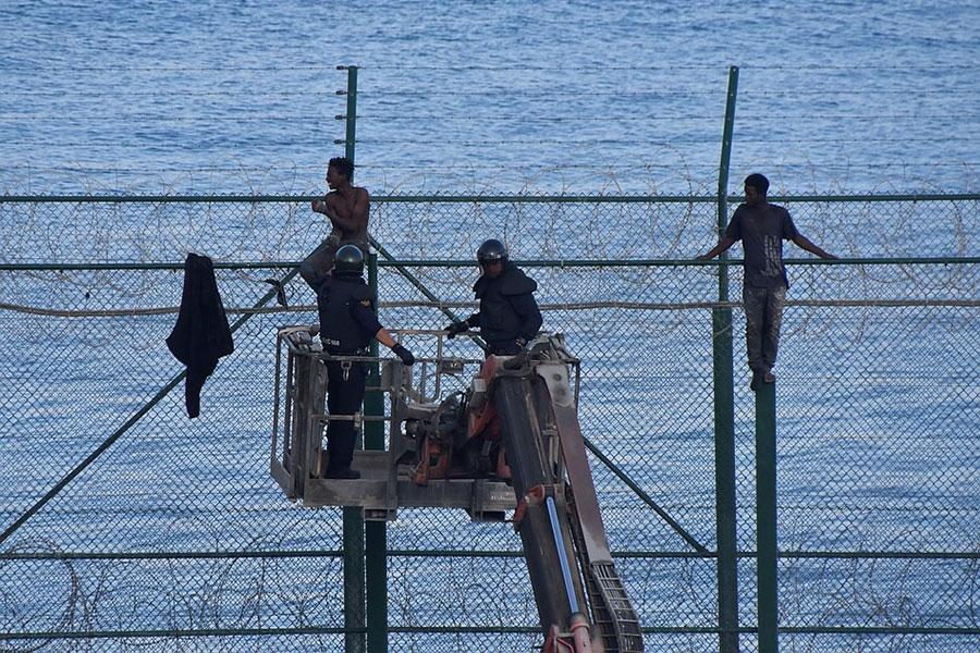 Колючая проволока и мигранты на заборе в Сеуте