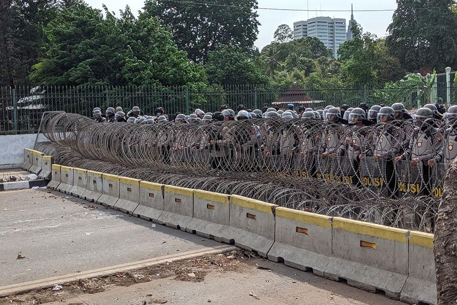 Колючая проволока и полиция защищает парламент в Индонезии от студентов